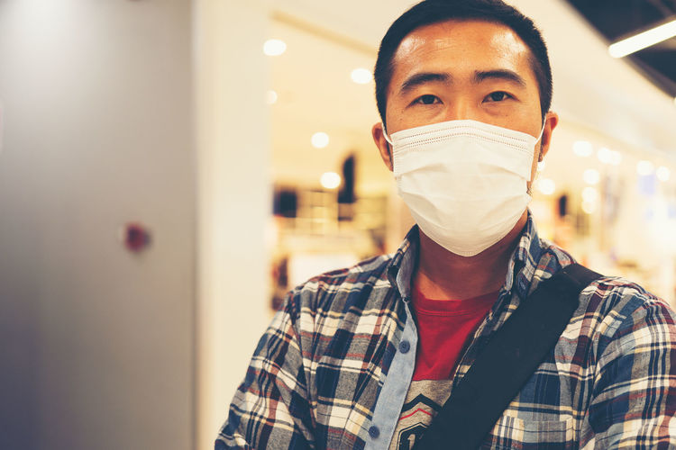 Portrait of man wearing mask standing at store