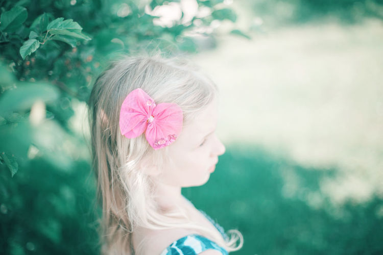 Close-up of girl with pink flower