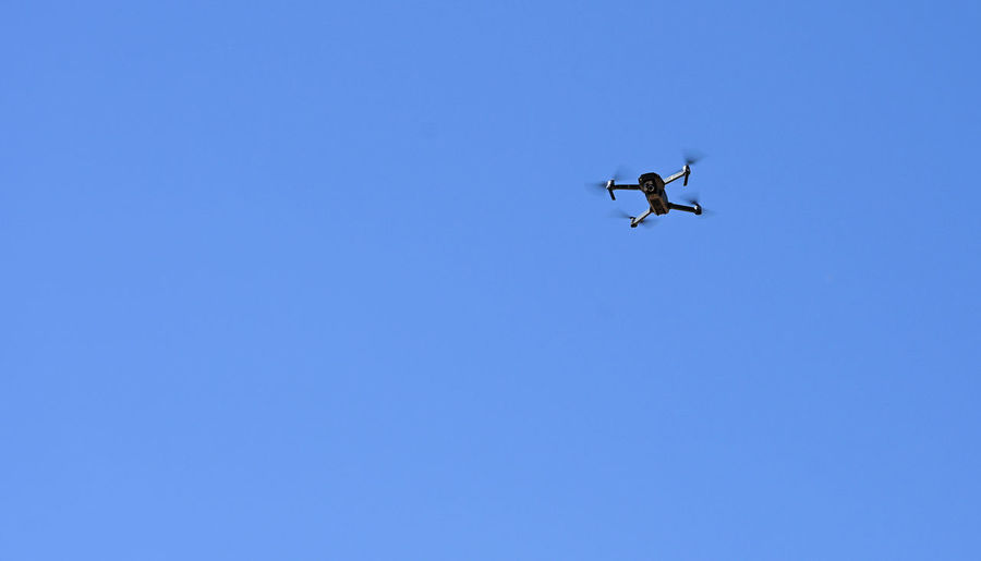 They're capturing the area with the Drone up in the air. Blue Low Angle View Sky Flying Copy Space Clear Sky Mid-air Motion Transportation Air Vehicle Mode Of Transportation No People Day Nature on the move Drone  Technology Camera Toy Photography
