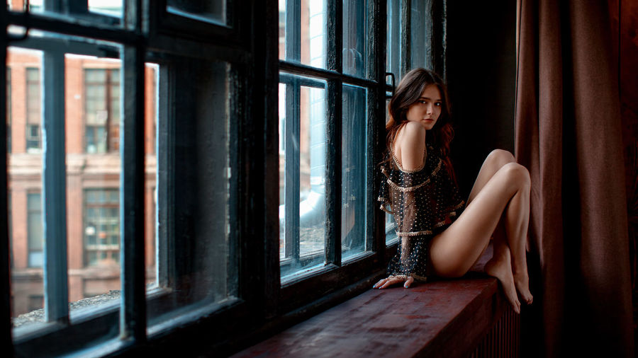 Portrait of sensuous young model wearing lingerie while sitting on window sill at home