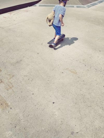 Rear view of boy skateboarding at playground during sunny day