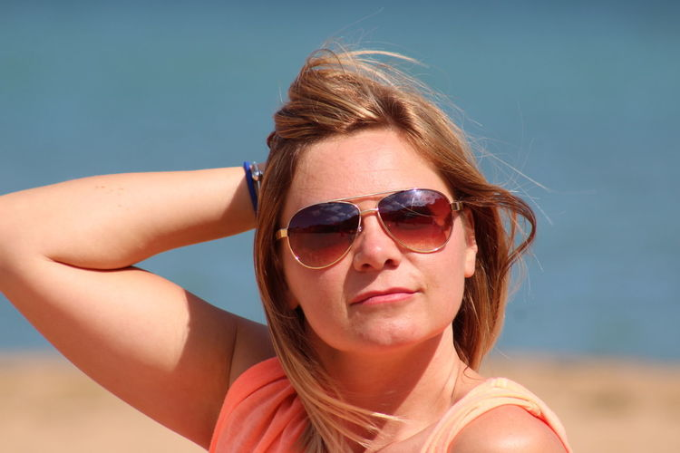 Portrait of mid adult woman wearing sunglasses at beach