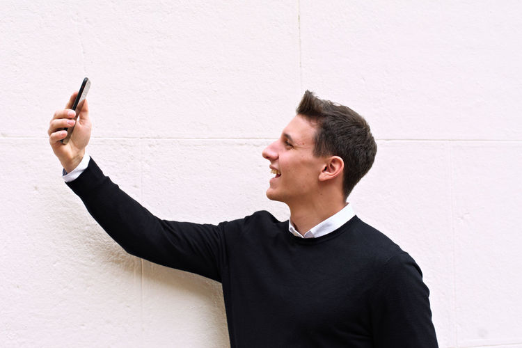 Young man using mobile phone against wall
