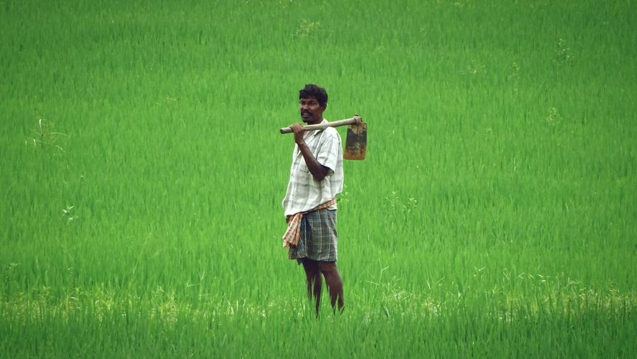 Portrait Of Farmer With Shovel Standing On Rice Farm
