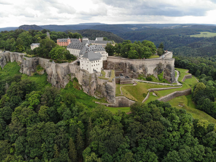 High angle view of castle on mountain against cloudy sky