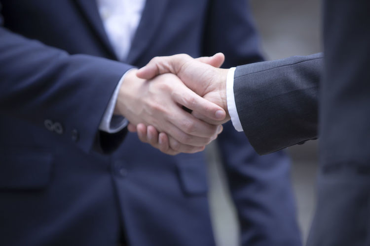Midsection of businessman shaking hand with colleague