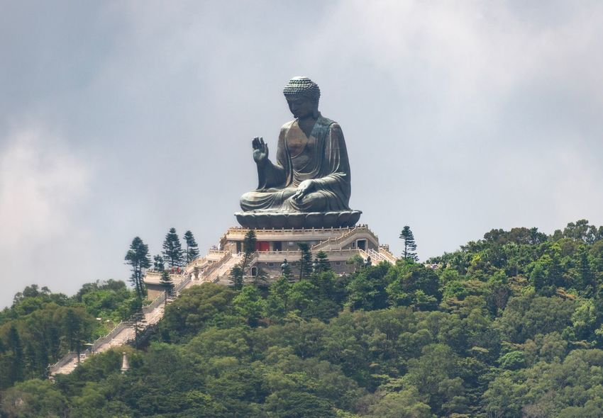 Big Buddha Overview Tian Tan Buddha Tree Religion Plant Place Of Worship Spirituality Belief Sky Architecture Built Structure Low Angle View Sculpture Human Representation No People Nature Representation Statue Art And Craft Outdoors