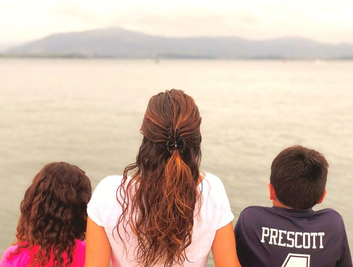 The mother, the daughter and the son looking the sea