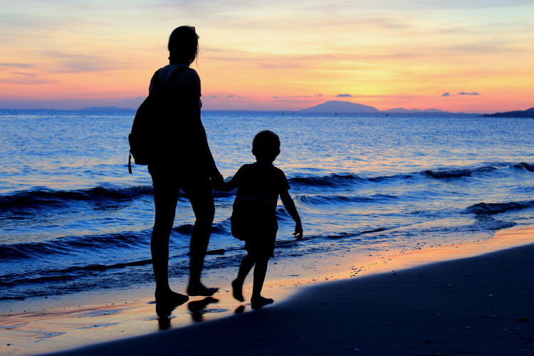 Mother & son. Strolling Along The Beach Muine, Vietnam  Sunset_captures Mother & Son Travel Photography Travel EyeEmNewHere Holiday Summerholiday Water Sea Full Length Sunset Togetherness Beach Wave Bonding Multi Colored Low Tide Coastal Feature Coast Romantic Sky Tide Shore Family Bonds Seascape Dramatic Sky Coastline