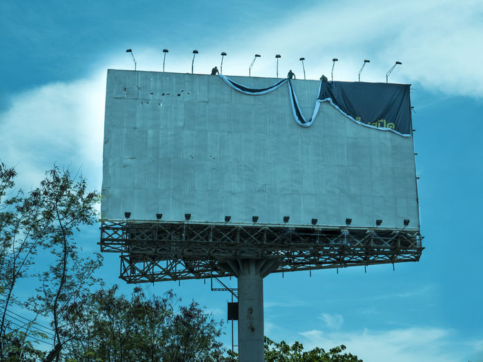 Sky Cloud - Sky Architecture Built Structure Low Angle View Nature Plant Day Billboard Tree Blue Outdoors Building Exterior Communication Roof Damaged Advertisement Fuel And Power Generation White Color Workers