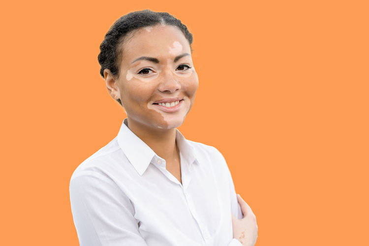Portrait of young woman suffering from dermatitis standing against orange background