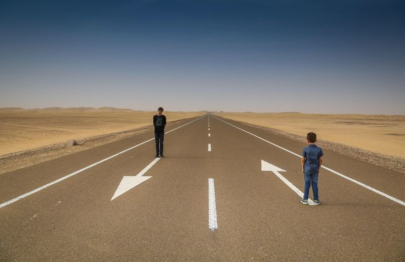 Brothers standing on road arrow symbols along landscape against clear blue sky