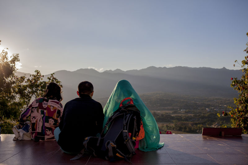 Rear view of friends sitting at observation point against mountains