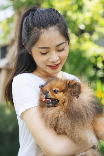 Young woman holding dog standing at park
