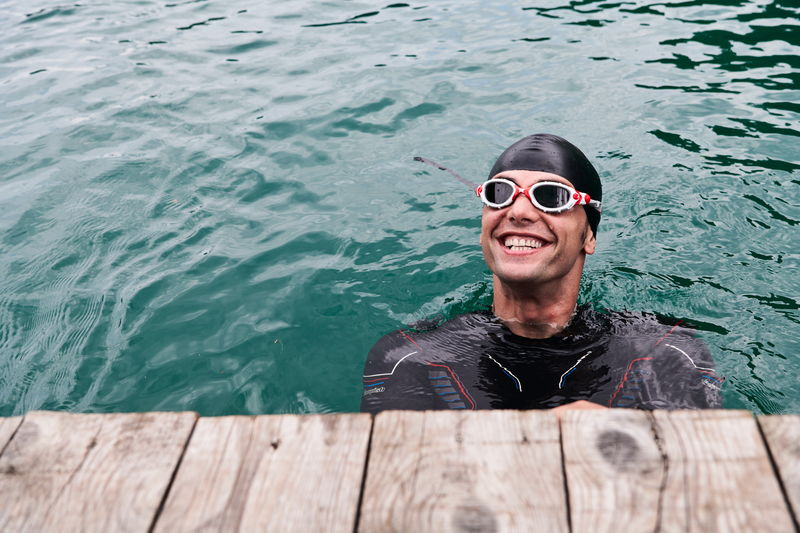 Portrait of smiling man swimming in water
