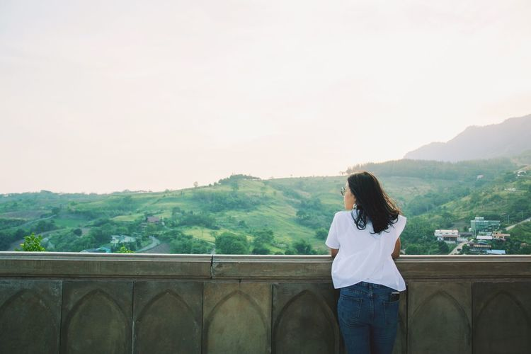 Rear view of woman standing on railing against mountain