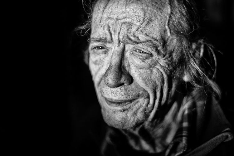 Close-Up Of Crying Senior Man Looking Away Against Black Background