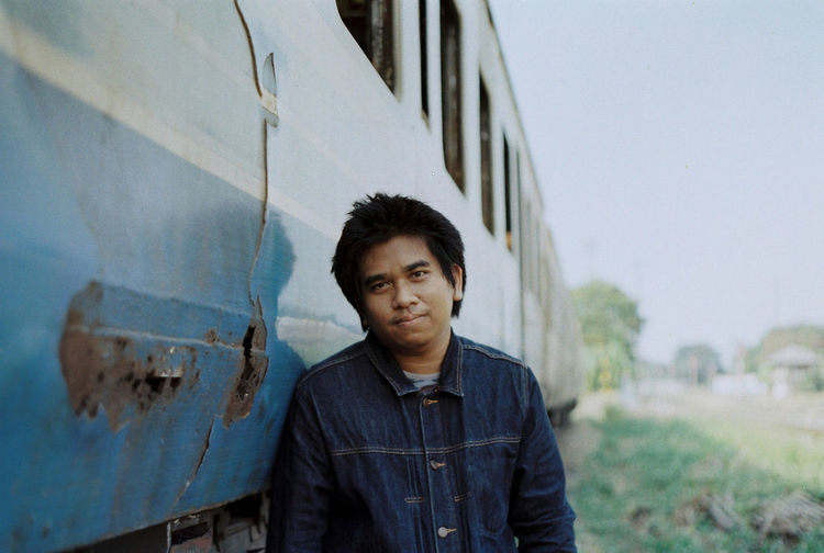 Portrait of young man standing by old weathered train