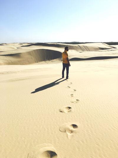 Full length rear view of man standing on desert