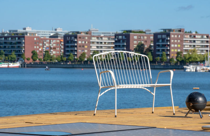 Chairs By Sea Against Buildings In City