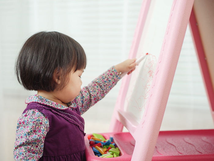 Cute Girl Writing In Whiteboard At Home