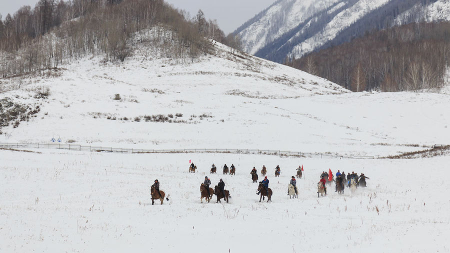 People riding horses on snowcapped landscape