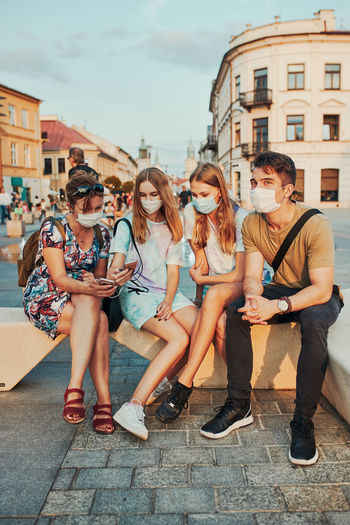 Family spending time together sitting in the city center. girls wearing the face masks