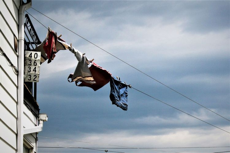 Low Angle View Of Laundry Hanging On Clothesline Against Cloudy Sky