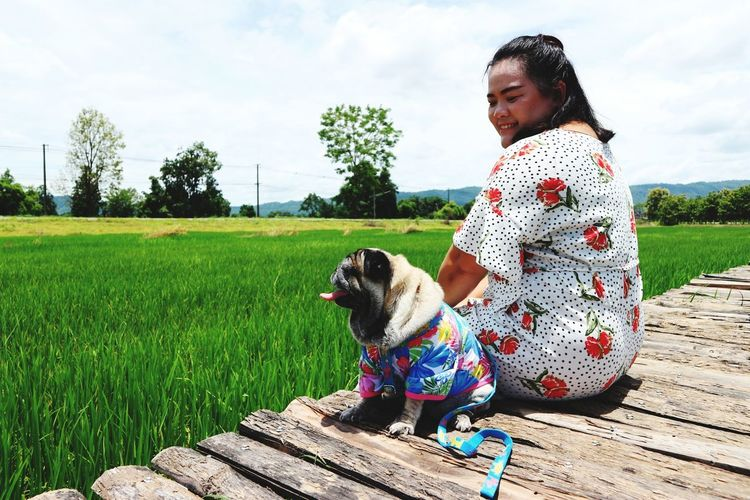 Smiling woman with dog sitting on boardwalk by paddy field