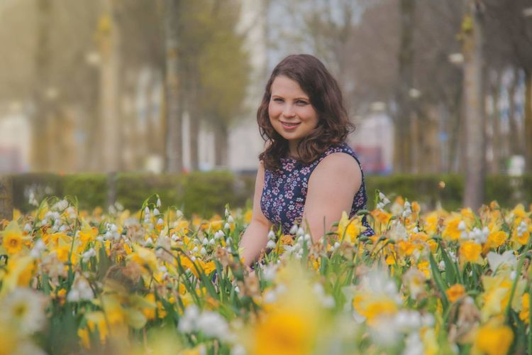 Portrait of smiling girl with yellow flowers on field