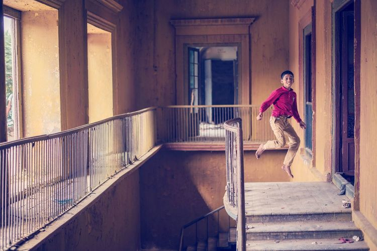 Portrait of teenage boy jumping in abandoned building
