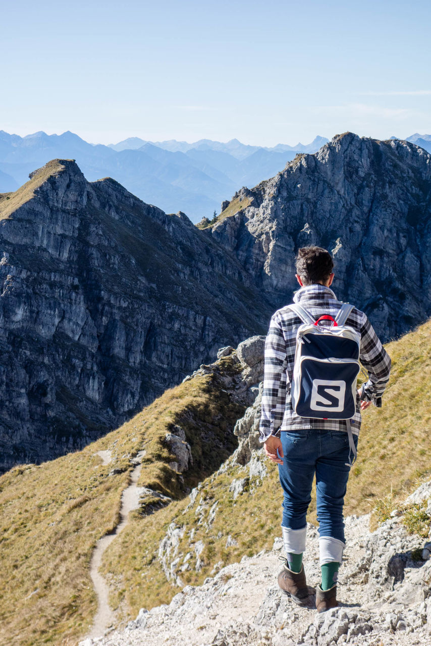 mountain, mountain range, rear view, adventure, rock - object, hiking, one man only, scenics, one person, adult, activity, full length, men, nature, only men, adults only, sport, standing, mountain peak, young adult, people, day, outdoors, beauty in nature, climbing, extreme sports, sportsman, sky