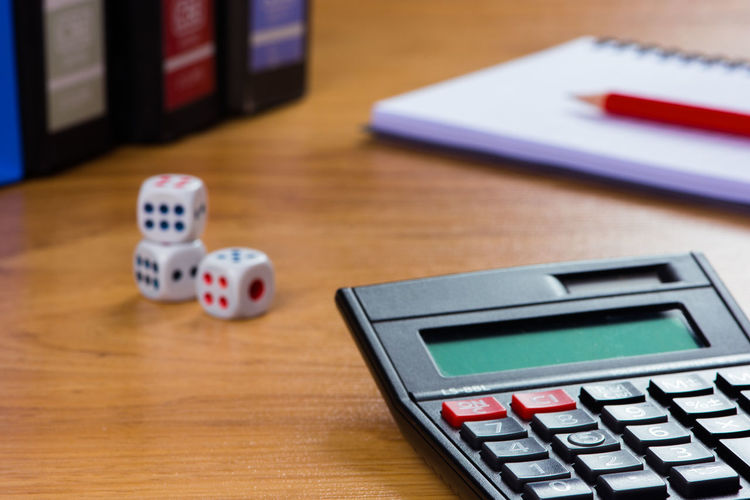 Dice, calculator and book on the table