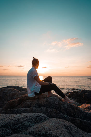 Sunset Sky Sitting Real People Sea Water Lifestyles Beach Beauty In Nature Leisure Activity One Person Solid Rock Rock - Object Full Length Land Relaxation Scenics - Nature Young Adult Horizon Over Water Outdoors Looking At View