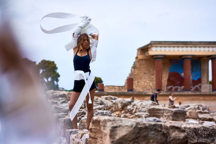 Minoan Architecture Minoan Palace Adult Archeological Site Architecture Arms Raised Beautiful Woman Building Exterior Built Structure Casual Clothing Day Hairstyle Human Arm Leisure Activity Lifestyles Motion Nature One Person Outdoors Real People Sky Standing Women Young Adult Young Women