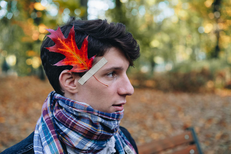 Side view of man with leaf stuck on face looking away