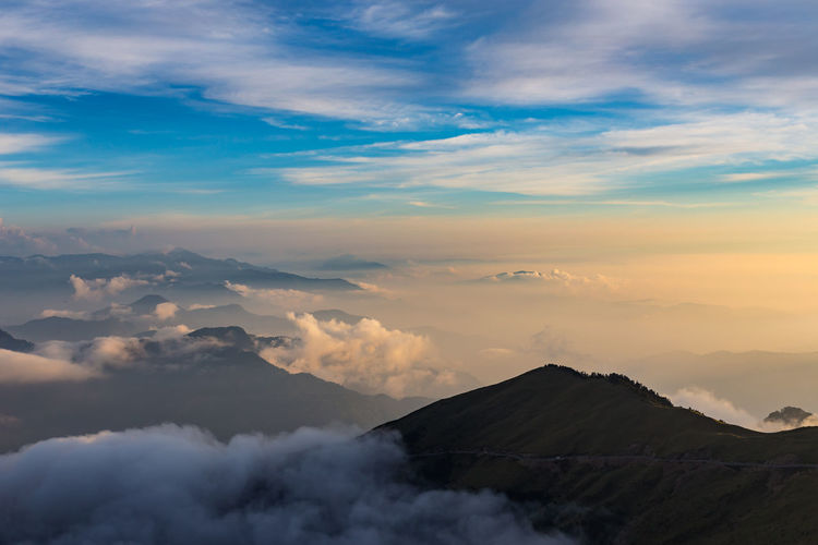 Aerial view of clouds covering volcanic landscape against sky during sunset