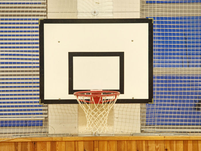 Basketball hoop in the high school gym. safety nets over windows. iluminated by fluorescent lighting