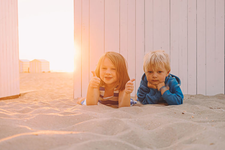 Portrait of siblings lying on sandy beach