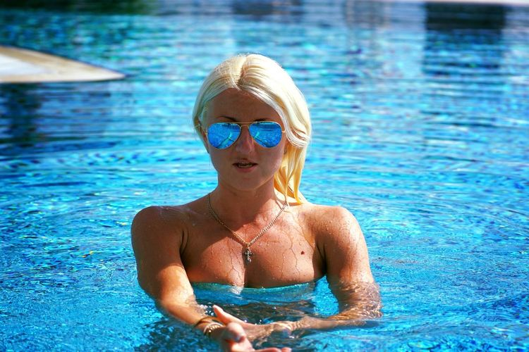 Portrait Of Beautiful Woman Wearing Sunglasses In Swimming Pool