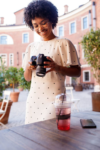 Holding One Person Technology Drink Wireless Technology Outdoors Smiling Lifestyles Table Blogger African American Girl Young Standing Front View Young Women