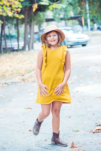 Cheerful girl looking away while walking on road
