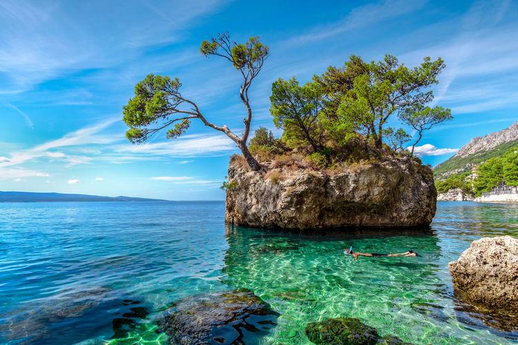 Man snorkeling in adriatic sea in front of brela stone