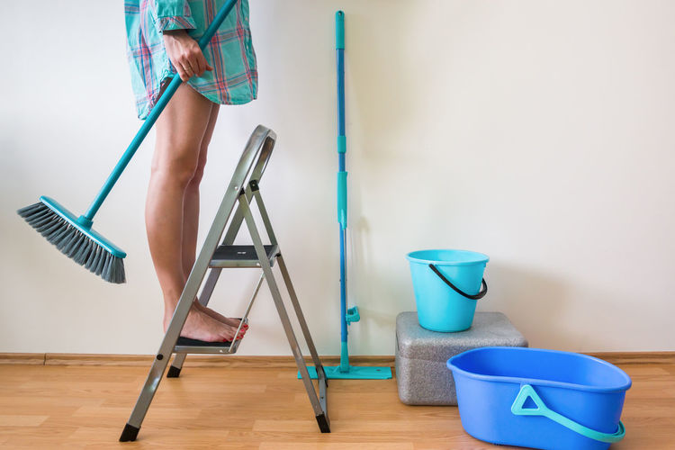 Low Section Of Woman Standing On Ladder While Cleaning Home