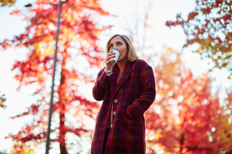 Autumn Beauty In Nature Change Day Focus On Foreground Leaf Low Angle View Nature One Person One Young Woman Only Outdoors People Real People Sky Standing Tree Young Adult Young Women