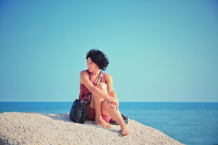 Full Length Of Thoughtful Woman Looking Away While Sitting On Rock Against Sea