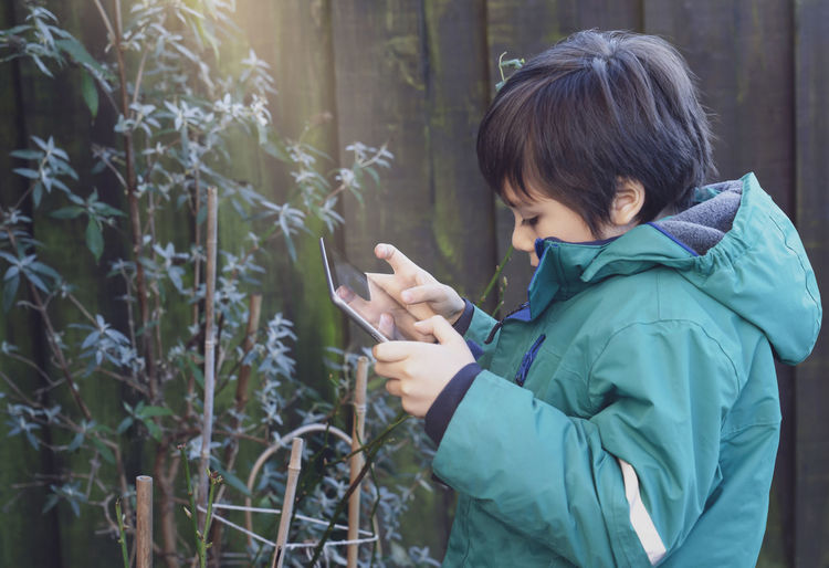 Side view of boy using digital tablet by plants outdoors
