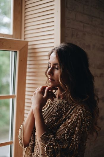 young beautiful girl by the window One Person Young Adult Lifestyles Real People Young Women Women Leisure Activity Indoors  Beauty Portrait Beautiful Woman Window Adult Hairstyle Headshot Looking Looking Away Casual Clothing Contemplation