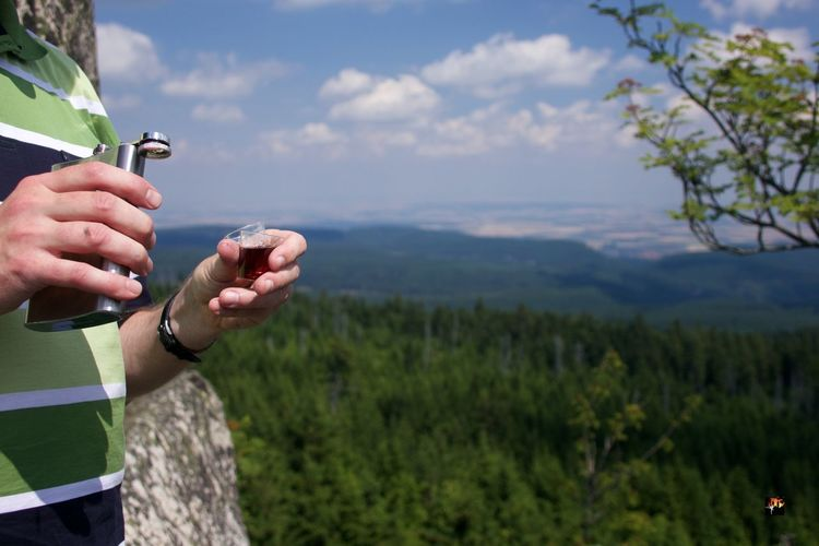 Midsection of man holding hip flask against mountain