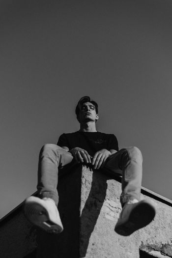 Low angle view of man sitting against sky